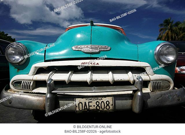 An old American car with the beach of Juangriego in the Caribbean coast on the island Margarita, Venezuela