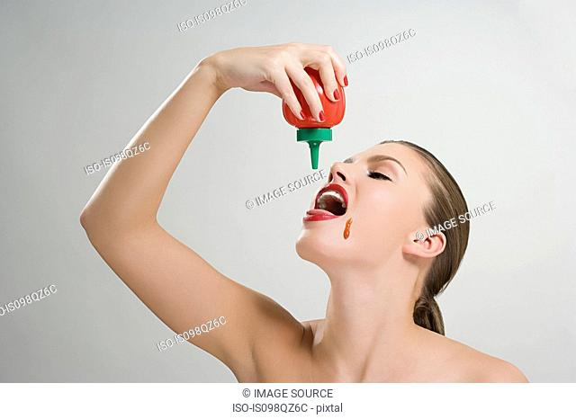 Woman pouring tomato ketchup into her mouth