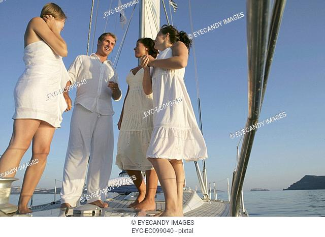 Four happy friends having a conversation on a boat