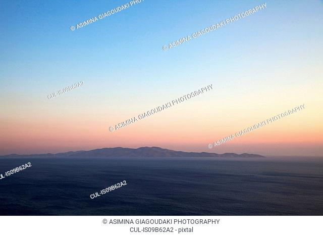 Seascape and distant view of Andros Island from Tinos Island at sunset, Greece