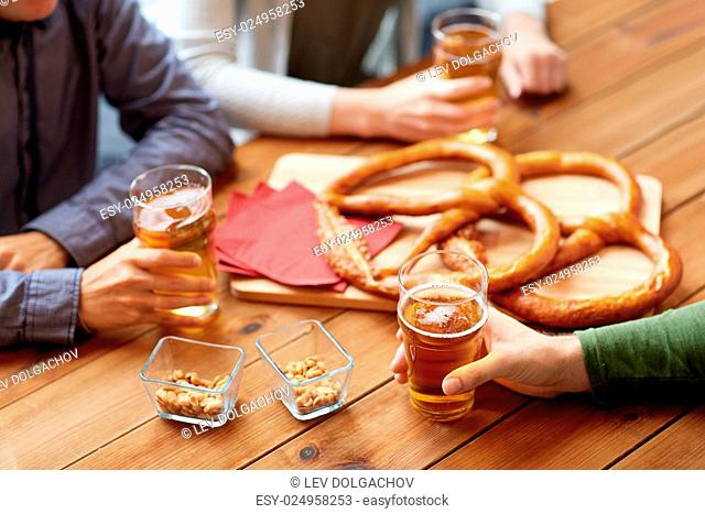 people, leisure and drinks concept - close up of male hands with beer glasses, pretzels and peanuts at bar or pub