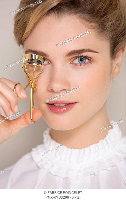 Beautiful woman curling her eyelashes with a curler