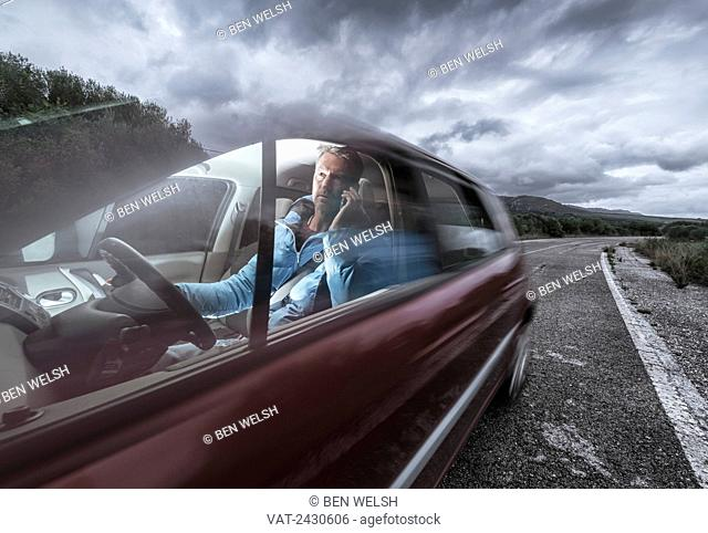 A man talking on his phone while driving; Tarifa, Cadiz, Andalusia, Spain