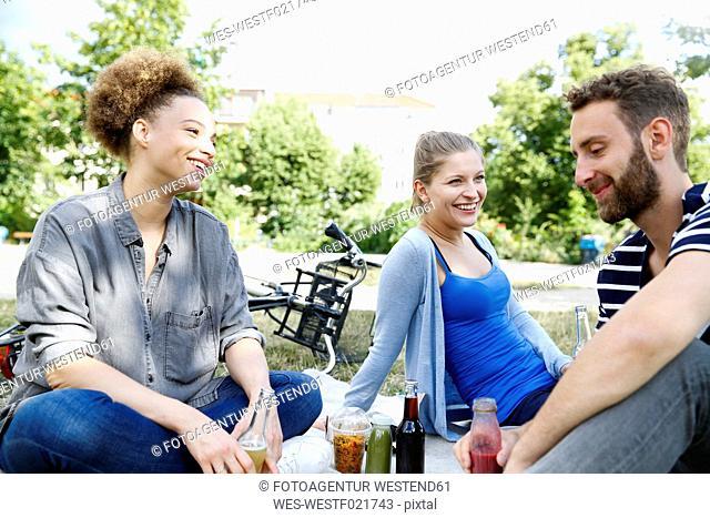Three happy friends drinking in park