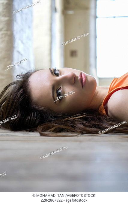 Sad young woman laying down on the floor