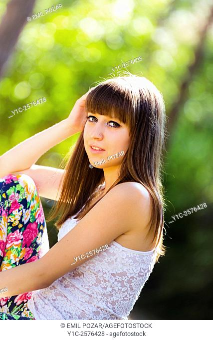 Cute teen-girl in in park looking at camera