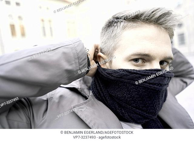 man with scarf in over mouth, in Munich, Germany