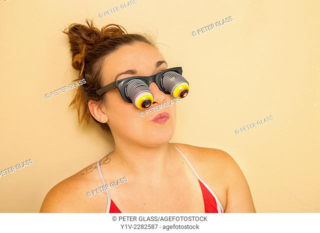 Young woman wearing funny glasses with bulging eyes