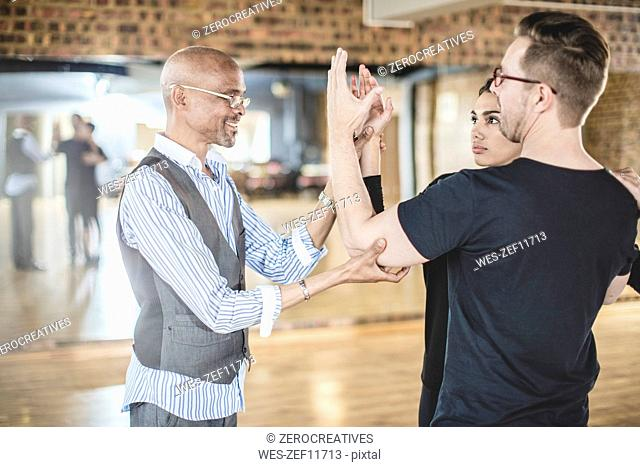 Dance instructor leading couple in dance studio