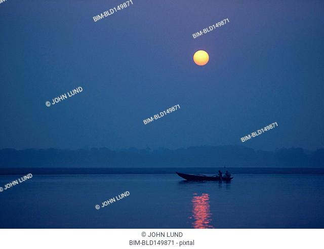 Silhouette of boat on water under glowing sun