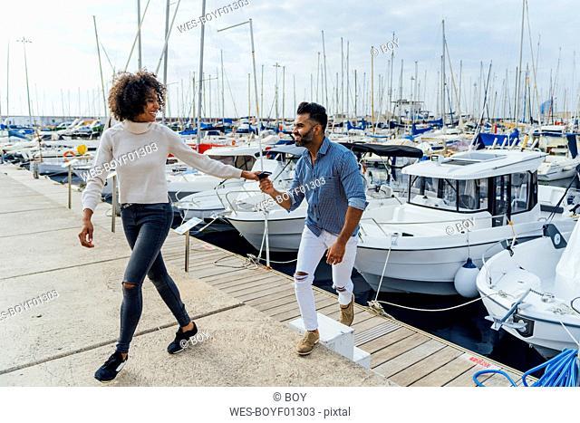 Spain, Barcelona, happy couple having a walk at the marina