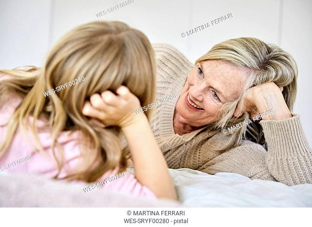 Senior woman relaxing with her granddaughter on the bed