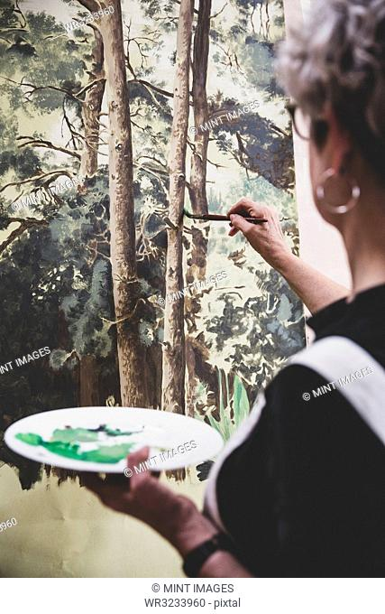 Senior woman wearing glasses, black top and white apron standing in studio, working on painting of trees in forest