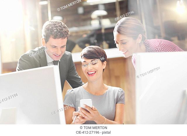 Business people texting with cell phone in office