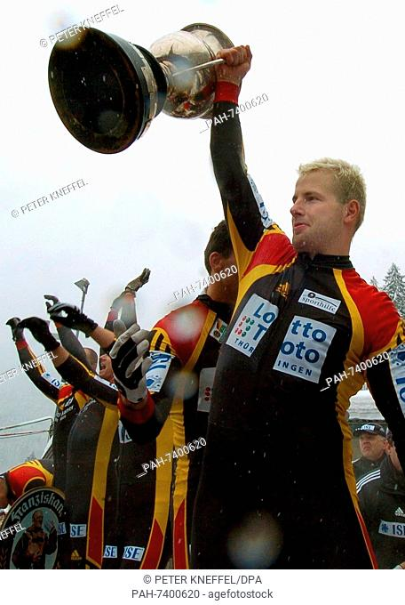 (dpa) German Andre Lange holds the World Cup trophy and jubilates on the  podium at the four-men Bobsleigh World Cup in Koenigsee 8f65ce474