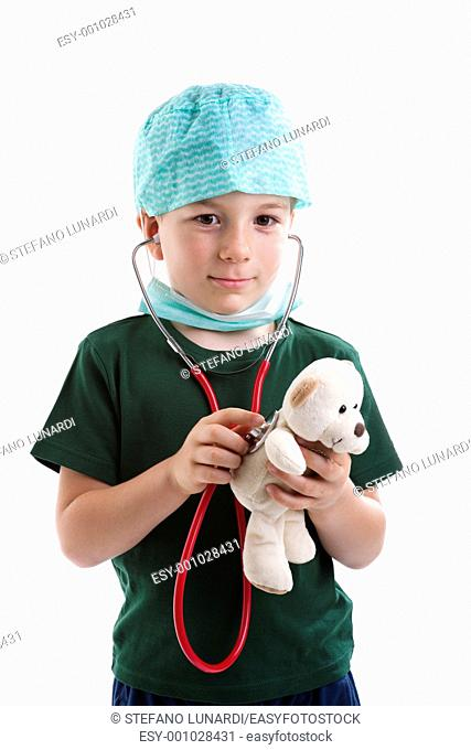 Little boy dressed as surgeon listening to his teddy's health