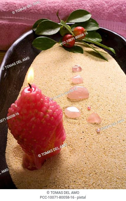 Spa elements, Budha head candle and pink stones in a bowl of sand, with leaf and berries and pink towel