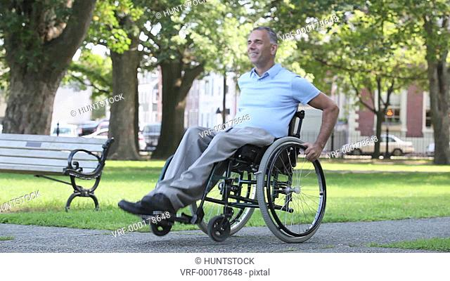 Man with spinal cord injury in a wheelchair doing tricks in chair while in outdoor park