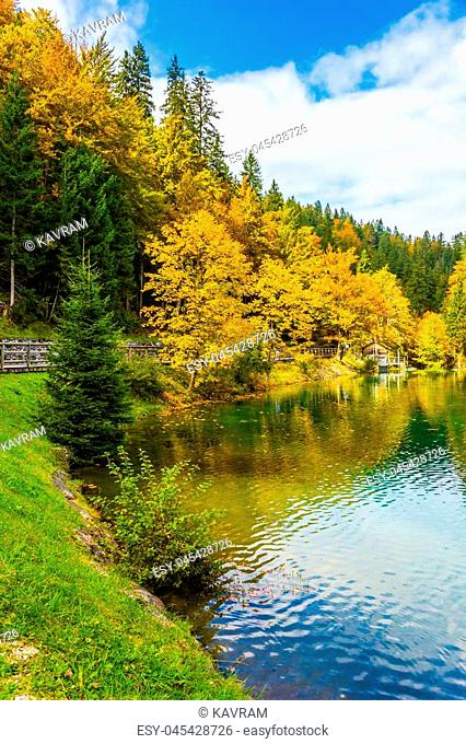 The smooth surface of the water reflects multicolored forests. The quiet lake in Northern Italy, Lago de Fusine. Concept of cultural and ecological tourism