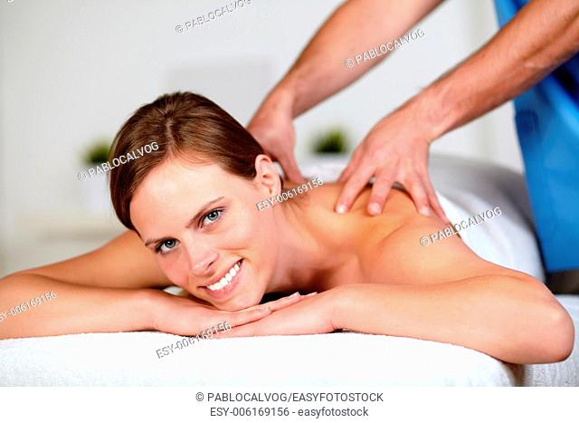 Close up portrait of a beautiful young woman getting a massage at spa resort