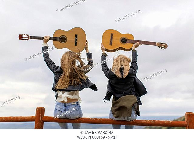Two women sitting on wooden fence lifting up guitars
