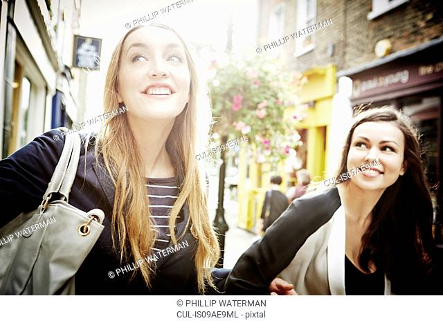 Young women walking down street carrying bags and laughing