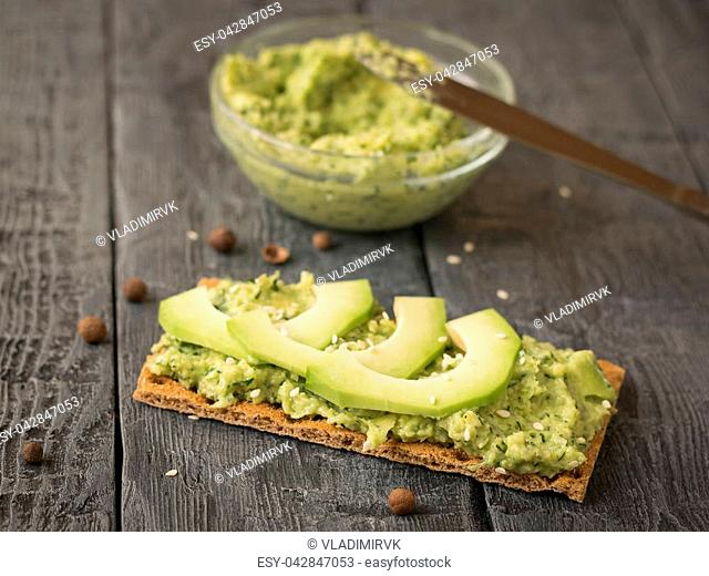 Cream puree avocado with parsley, dill and garlic in a bowl on a vintage table. The dish is vegetarian diet. Diet for weight loss