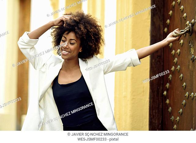 Spain, Cadiz, portrait of fashionable young woman with curly brown hair in front of house