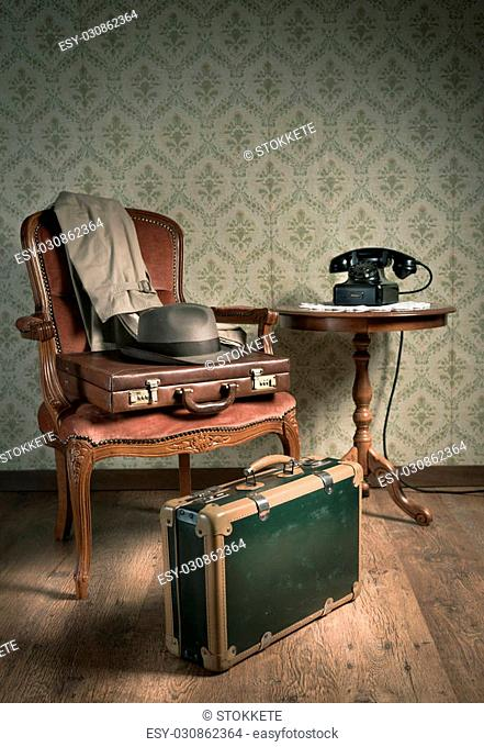 Male hat and suitcases on elegant armchair in a vintage style room