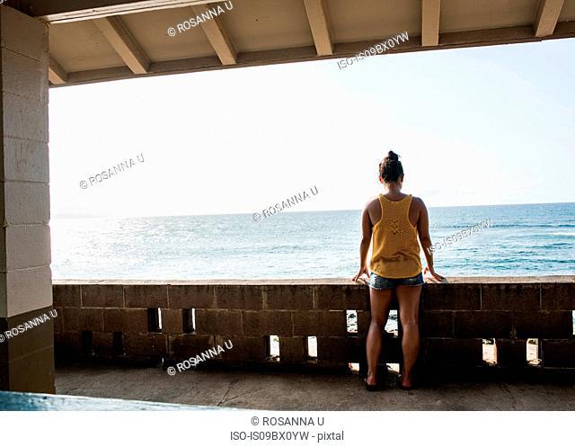Woman looking at sea from balcony, Hookipa Beach, Maui, Hawaii