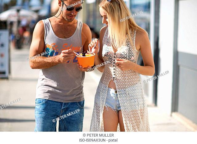 Couple strolling and eating frozen yoghurt on sidewalk, Venice Beach, California, USA