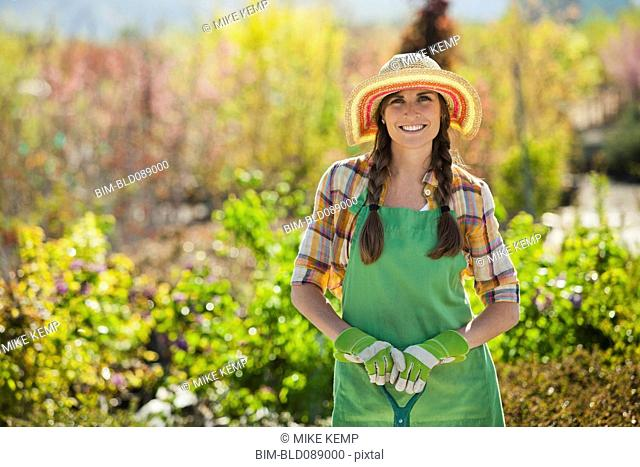 Caucasian woman standing with shovel in plant nursery