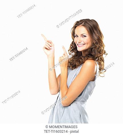 Studio portrait of beautiful smiling woman pointing upwards