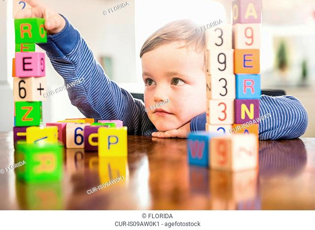 Boy playing with alphabet bricks at kitchen table