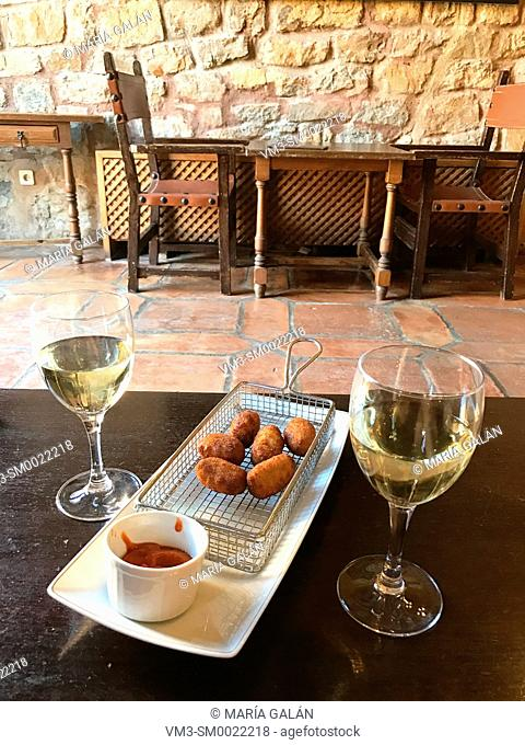 Two glasses of white wine and croquettes serving in a bar. Sigüenza, Spain