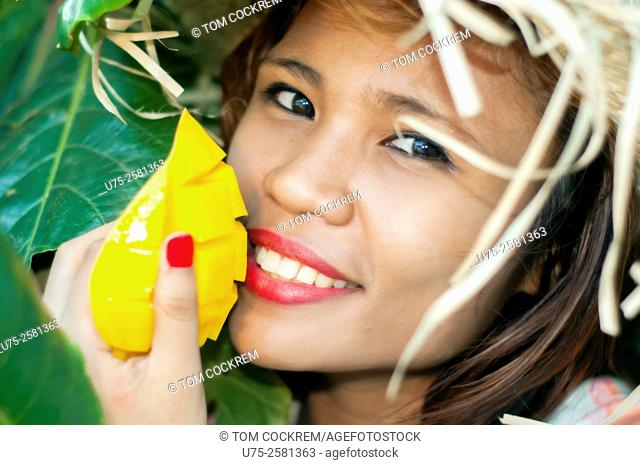 Young Asian woman with fresh mango, on location, Cebu, Philippines