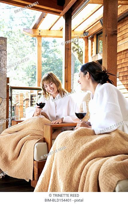 Women drinking red wine on spa deck