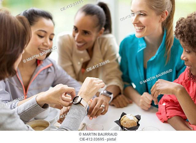 Smiling women friends looking at smart watches in cafe