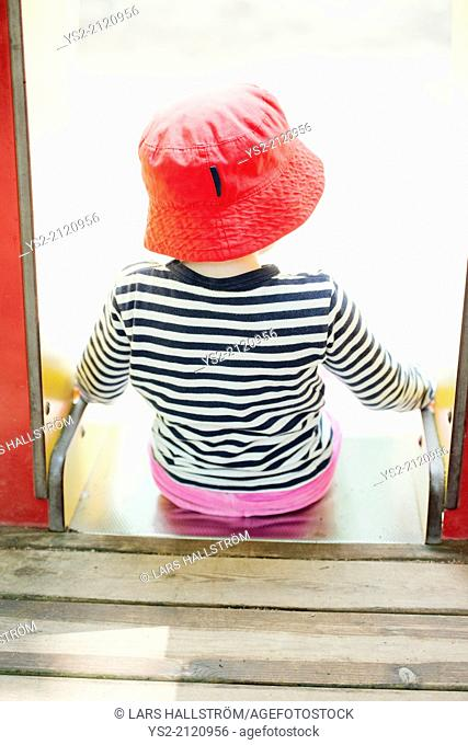 Childhood lifestyle moment. Little girl in read hat sitting at the top of a slide in a playground for children