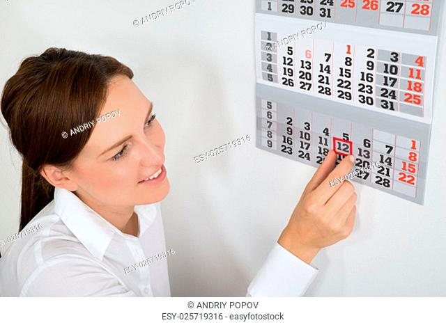 Close-up Of Young Businesswoman Placing Red Mark On Calendar Date