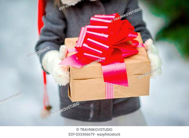 Cute little girl with christmas box gift in winter day