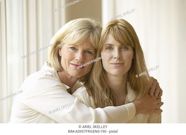 Mother hugging adult daughter indoors
