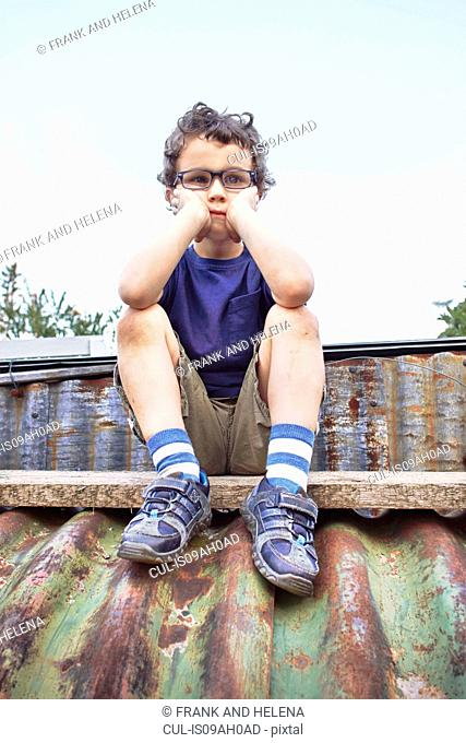 Glum little boy sitting on roof