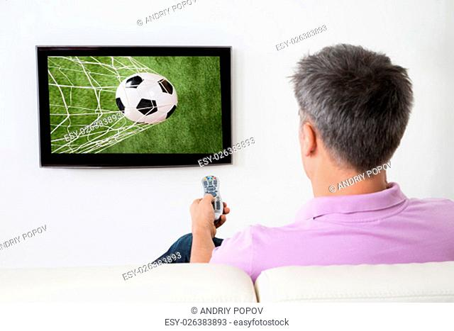 Man Watching Soccer Game On Television At Home