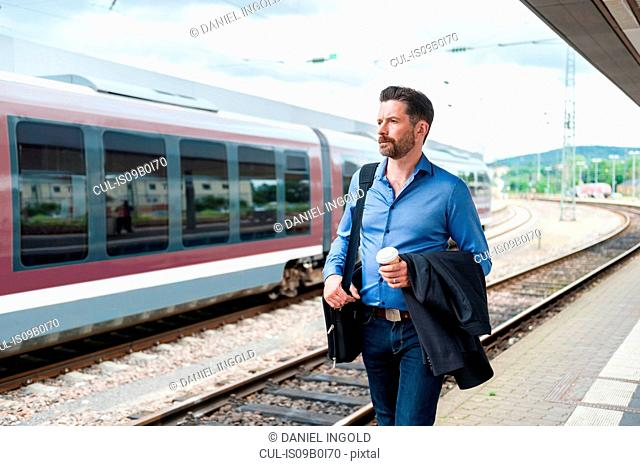 Mature businessman with takeaway coffee walking along on railway platform