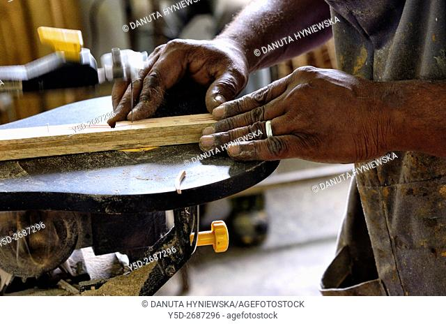 close-up of working man's hands, factory of handmade scale model wooden ships in Curepipe, Mauritius, Africa