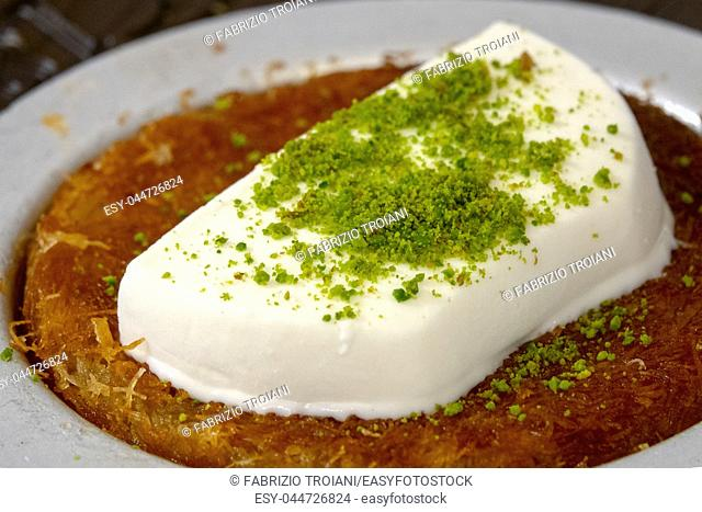 Close up of a Kanafeh with ice cream and pistachios