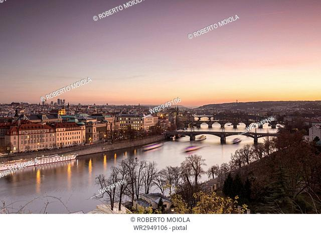 Pink sky on historical bridges and buildings reflected on Vltava River at sunset, Prague, Czech Republic, Europe