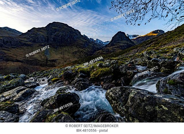 Small mountain stream in mountain landscape with peaks of Stob Coire nan Lochan and Stob Coire Sgreamhach, Glen Coe, west Highlands, Scotland, United Kingdom