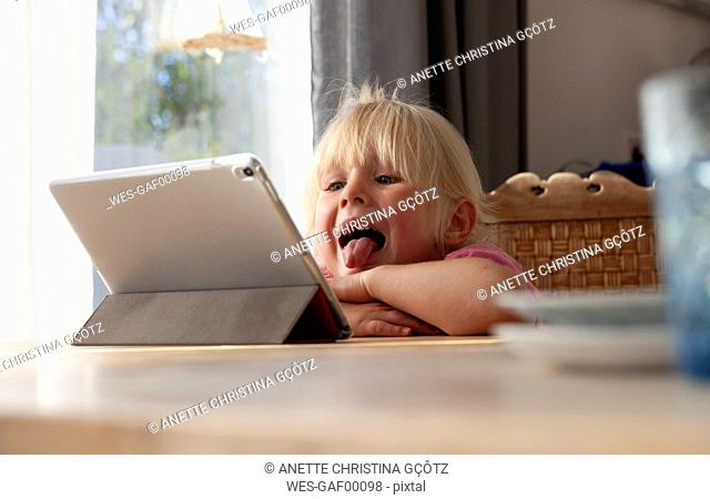 Portrait of blond little girl sticking out tongue while looking at digital tablet